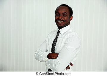 Happy african businessman with arms folded in office