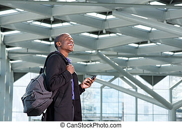 happy african businessman with mobile phone and bag