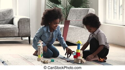 Happy african children playing toys sit on floor at home