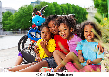 Happy African children resting after cycling