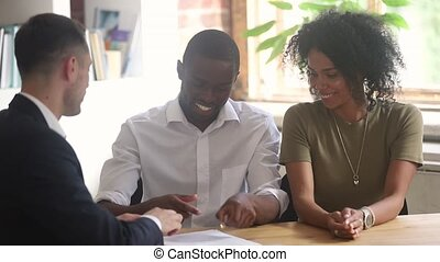 Happy african couple buying new house signing contract get keys