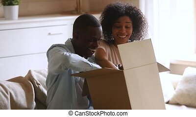 Happy african couple customers open cardboard box satisfied with purchase