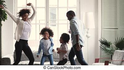 Happy african couple dancing with preschool children in living room
