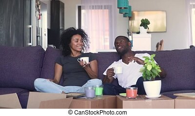 Happy african couple drinking coffee unpacking boxes in new home