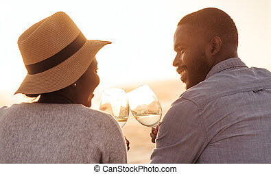 Happy African couple drinking wine and watching a beach sunset