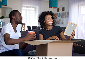 Happy african couple having fun unpacking boxes in living room