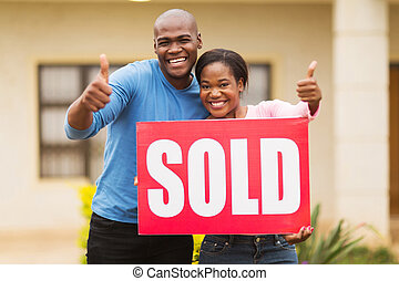 african couple outside home with sold sign