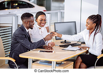 happy african couple with dealer buying car in auto show or salon
