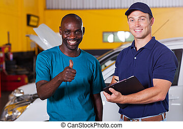 customer giving thumb up in car repair shop - happy african...