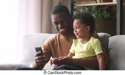Happy african dad and little son laughing looking at phone