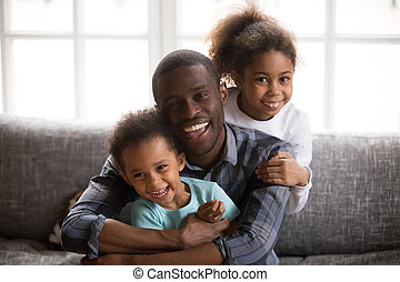 Happy african dad and mixed race children at home portrait