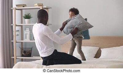 Happy african dad and son having pillow fight on bed