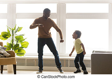 Happy african dad and toddler son dancing in living room