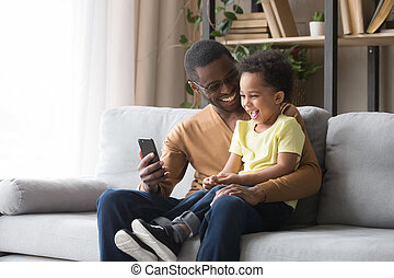 Happy african dad and toddler son laughing looking at cellphone