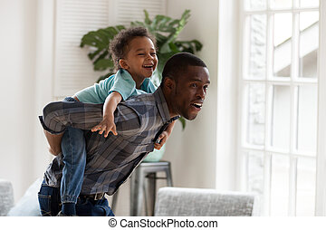 Happy african dad gives little son piggyback ride at home