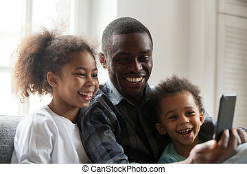 Happy african dad laughing using smartphone with kids at home