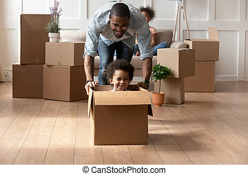 Happy african dad playing with little son riding in box