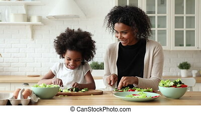 Happy african daughter and mum give high five cooking together