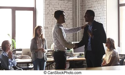 Happy african american employee get positive feedback from boss and team supporting black worker with handshake applause congratulate with promotion thank for good work, appreciation recognition concept