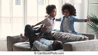 Happy african ethnic kids siblings doing exercises with strong father.