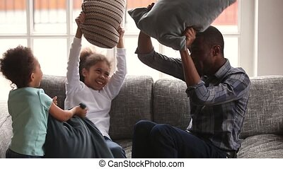 Happy african family dad and little children enjoying pillow fight
