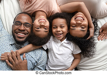 Happy african family lying on bed cuddling, portrait, top view