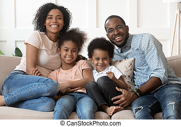 Happy african family of four looking at camera at home