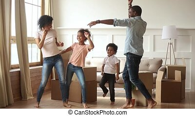 Happy african family parents and kids dancing celebrating moving day