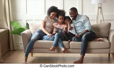 Happy african family parents and little children using digital tablet
