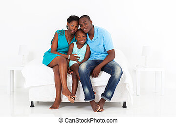 African family sitting on bed