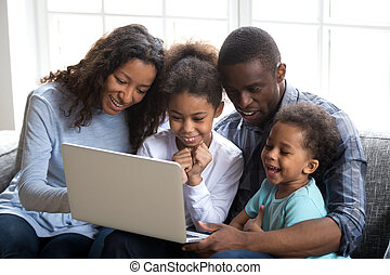 Happy african family with children using laptop together at home