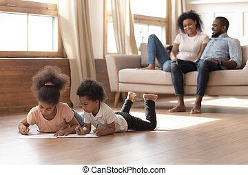 Happy african family with kids leisure activities in living room