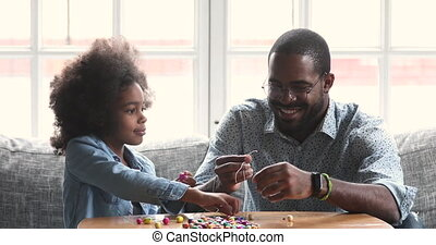 Happy african father and child daughter making necklace together