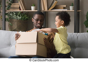 Happy african father and little son opening parcel at home