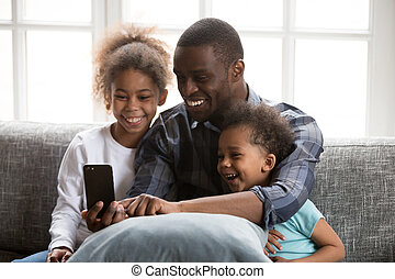 Happy African father with kids using smartphone - Happy...