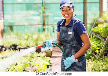 african female nursery worker watering plant