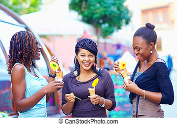 happy african friends eating ice cream outdoors