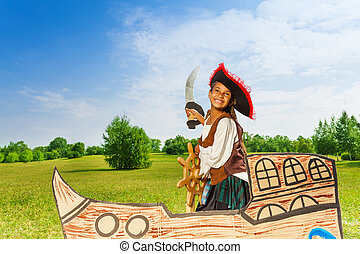 Happy African girl as pirate with hat and sword