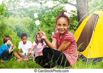 Happy African girl holding stick with marshmallow