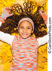 Happy African girl in maple yellow autumn leaves