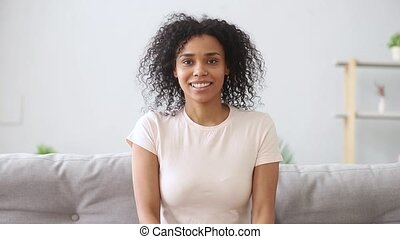 Happy african girl talking to webcam makes video call