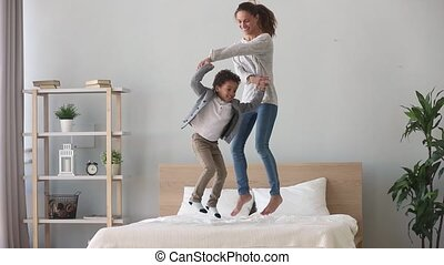 Happy african kid boy and caucasian mom jumping on bed