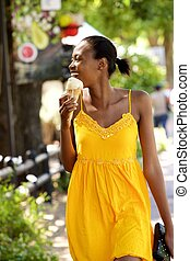 Happy african lady with ice cream on the street