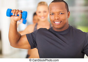 african man exercising in gym with dumbbell