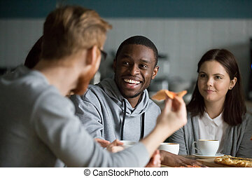 Happy african man laughing at friends joke hanging in pizzeria