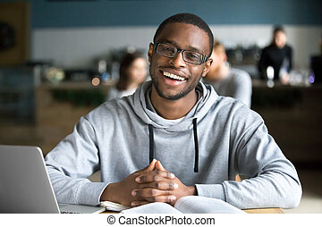 Happy african man sitting at cafe table looking at camera