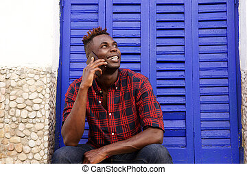 Happy african man sitting outdoors talking on mobile phone and looking away