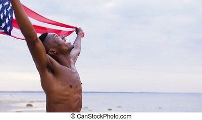 happy african man with american flag on beach - patriotism,...