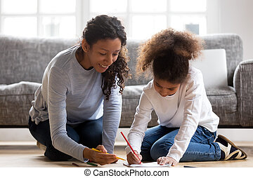 Happy african mom and mixed-race daughter drawing with colored p