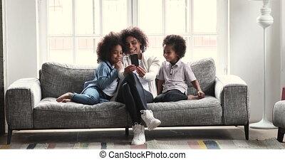 Happy african mum watching smartphone videos having fun with kids